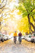 Two students ride down Greek Row in the fall, amid changing leaves.